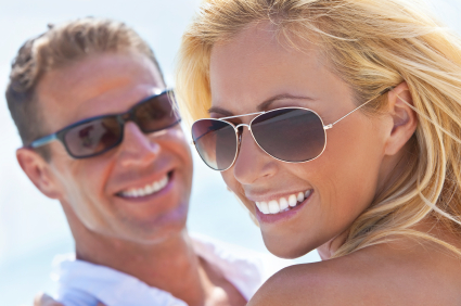 Man and woman smiling with sunglasses on the sunny day in Portland, OR. Learn more about how to contact us at Oregon Periodontics, P.C.
